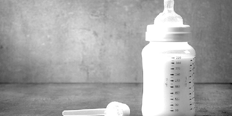 Bottle full of breast milk and a scoop full of dried formula