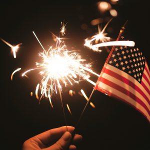 night sky hand holding lite sparkler and USA flag